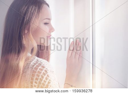 Beauty model girl portrait looking out the window. Young beauty romantic female looking away, close-up. Beautiful brunette young woman in sun light, curtains