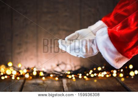 Christmas Santa Claus showing empty copy space on the open hands palm for text. Proposing product. Advertisement gesture presenting point. Holding gift, text or product over wooden background