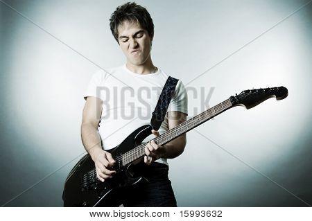 hombre guapo tocando en la guitarra. Studio disparó sobre fondo gris