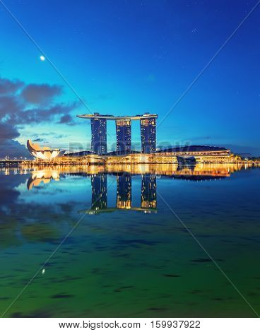 Singapore, Republic of Singapore - May 4, 2016: Marina Bay Sands hotel glowing at night reflecting in water