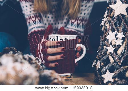 Crop shot of young woman in sweater sitting at Christmas table with mug.