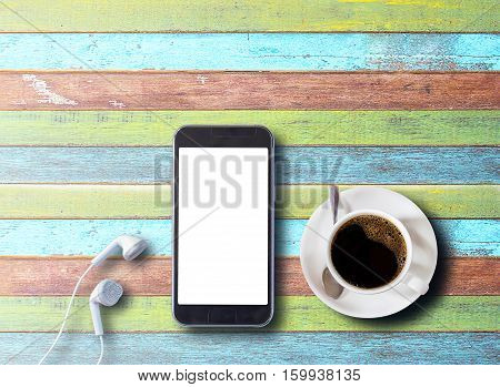 Cup of coffee with smartphone and earphones on colorful wood table background with copy space for any design. smart phone and coffee cup on wooden top view