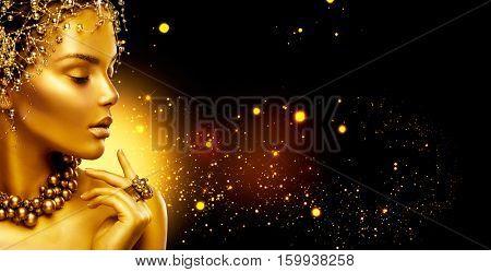 Gold Woman skin. Beauty fashion model girl with Golden make up, hair and jewellery on black background. Gold ring and necklace. Metallic, glance Fashion art portrait, Hairstyle and make up. poster