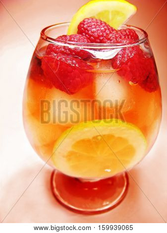 alcoholic red liqueur cocktail punch with ice and raspberry