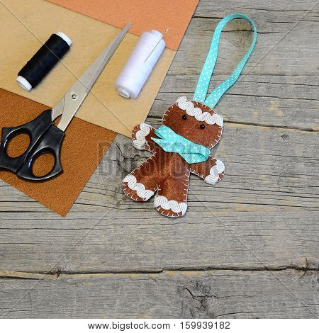 Christmas tree gingerbread man decor. Homemade hanging decor, scissors, thread, needle, brown felt pieces on old wooden table with copy space for text. Quick and easy Christmas sewing diy for kids