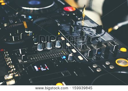 DJ CD player and mixer with DJ headphones close up