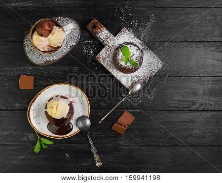 Chocolate lava cake (Molten) with ice cream on plate. Balls of ice cream in cup. Chocolate lava cake (Molten) with mint on board. Pieces of chocolate. Dark black wooden background. Top view blank space. poster