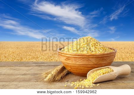 Bulgur or couscous in bowl. Bulgur in ceramic bowl and ears of wheat on table with field of wheat on the background. Golden wheat field and blue sky with beautiful clouds