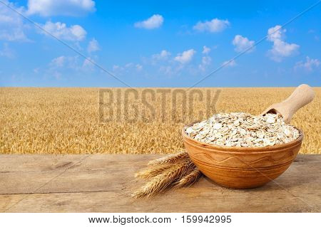 Oat flakes in bowl. Ears of oats and oatmeal in bowl on table with field on the background. Golden field and blue sky. Uncooked porridge
