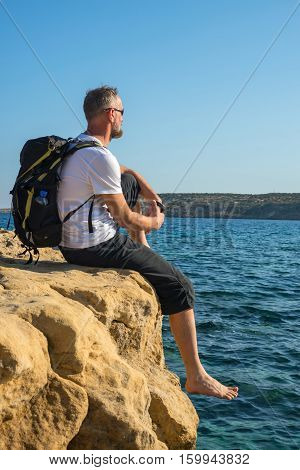 Bearded Man With Backpack Sits On Rocky Shore Barefoot