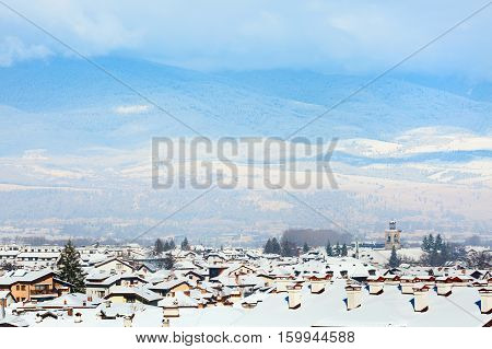 Houses with snow roofs and church tower panorama of bulgarian ski resort Bansko, Bulgaria