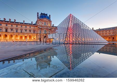PARIS - FEB 9 : Louvre museum at twilight in summer on February 92015. Louvre museum is one of the world's largest museums with more than 8 million visitors each year.
