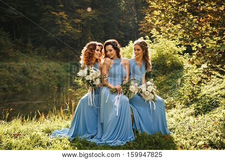 Three beautiful bridesmaids in the park on wedding day