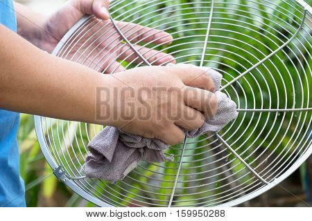 Man cleaning electric fan housework at home