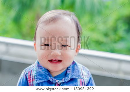 cute baby look somewhere and smile happily in the park asian