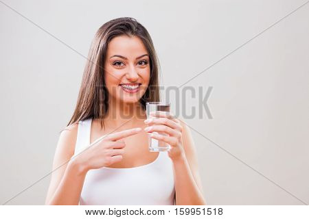 Portrait of young woman who is pointing at glass of water. Refreshment is important.