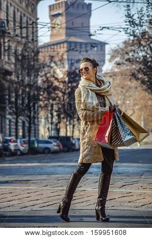 Rediscovering things everybody love in Milan. Full length portrait of smiling elegant traveller woman with shopping bags in Milan Italy looking into the distance poster