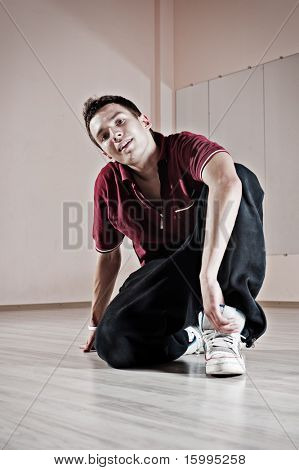 handsome breakdancer sitting on the floor. photo in dance studio poster