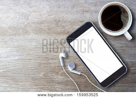 Smart phone and earphone with cup of coffee on old wooden background with copy space. top view
