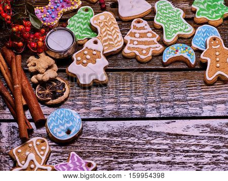 Christmas gingerbread cookies on woden table and candels. Angle with copy spice and cinnamon sticks.