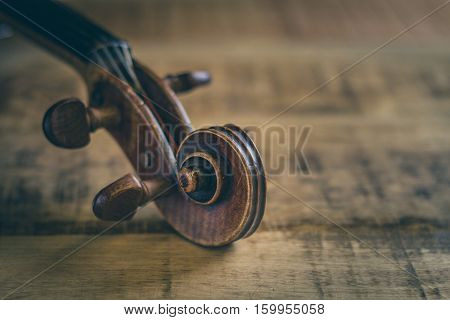 Tuning peg pegbox of old violin stringed musical instrument in close-up