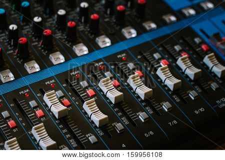 The audio equipment control panel of analog studio mixer side view. Close-up selected focus