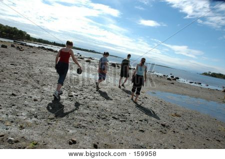 People Walking Through The Coastal Dirt And Sand