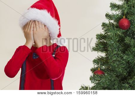 Little child in red Santa cap hidding his face with both hand near christmas tree