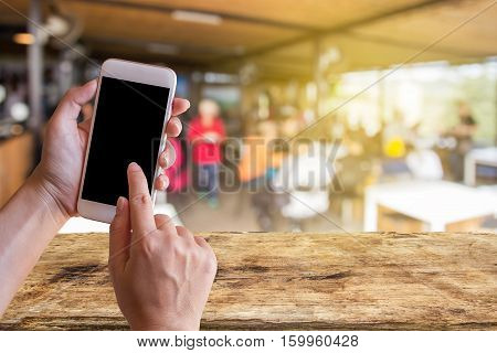 Women hand holding mobile smart phone with coffee shop blur background with copy space. Customer at restaurant blur background with bokeh vintage colorfood online call shopping