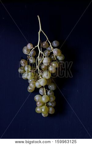 a bunch of green grape on a black background