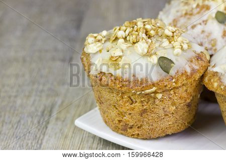 Closeup image of a small carrot cake on a wooden table.