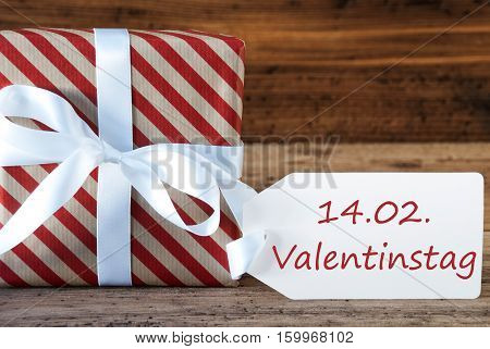 German Text Valentinstag Means Valentines Day. Macro Of Christmas Gift Or Present On Wooden Background. Card For Seasons Greetings, Best Wishes Or Congratulations. White Ribbon With Bow.