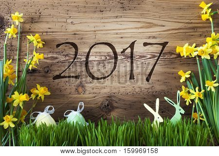 Wooden Background With Text 2017 For Happy New Year. Easter Decoration Like Easter Eggs And Easter Bunny. Yellow Spring Flower Narcisssus With Gras. Card For Seasons Greetings