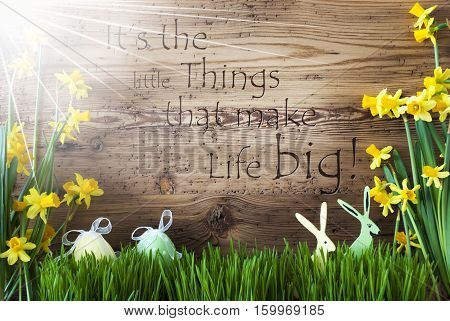 Wooden Background With English Quote It Is The Little Things That Make Life Big. Easter Decoration Like Easter Eggs And Easter Bunny. Sunny Yellow Spring Flower Narcisssus With Gras.
