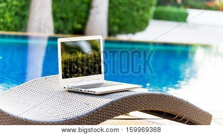 netbook near to swimming pool, select and soft focus