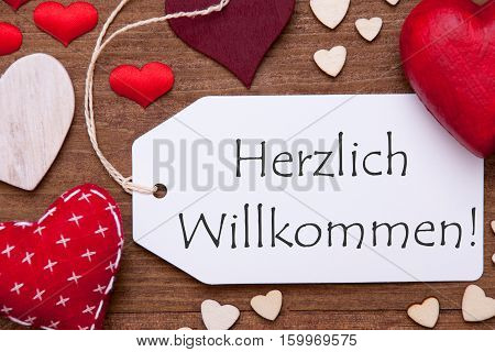 Label With German Text Herzlich Willkommen Means Welcome. Red Textile Hearts On Wooden Background. Flat Lay With Retro Or Vintage Style