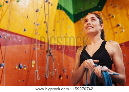 Perfect day. Overjoyed pretty delighted woman using climbing equipment while standing in climbing gym and smiling.