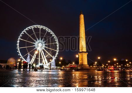 Christmas in Paris France. Place de la Concorde in Paris France at night. In the center of the square stands giant Egyptian obelisk decorated with hieroglyphics. Illuminated Ferry Wheel