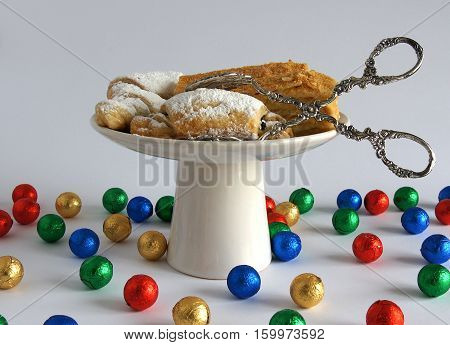 Homemade pastries on a white ceramic plate with kitchen serving tongs and multicolored bright balls