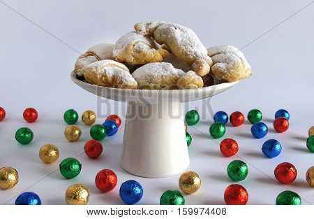 Homemade pastries on a white ceramic plate and multicolored bright balls