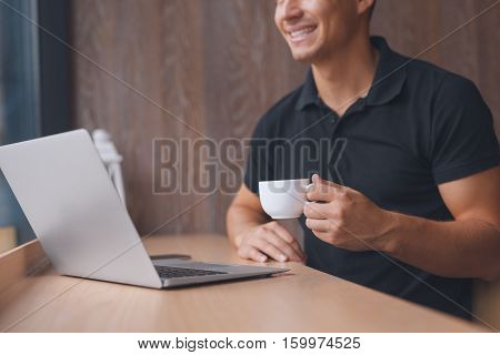 Selective focus on coffee cup. Casual man working on laptop and holding cup of coffee while sitting in cafe. Cropped unrecognizable portrait. Faded filter
