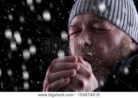 Freezing cold man standing in a snow storm blizzard trying to keep warm. Eyes closed and blowing warm air into his hands. Wearing a beanie hat and winter coat with frost and ice on his beard and eyebrows. Looking to the left.
