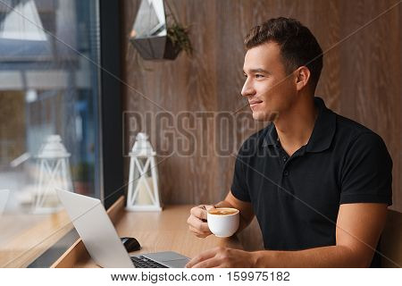 Young handsome man sitting in cafe with a cup of coffee looking outside the window. Working at laptop and having a little break with copy space