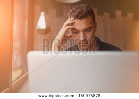 handsome hipster modern man designer working inside cafe at window using laptop. close up face of Puzzled man thinking while sitting at computer with copyspace