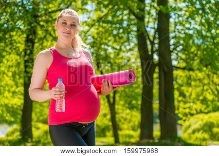 Pregnant Woman Caucasian Appearance With A Mat And Water After Exercising In Nature