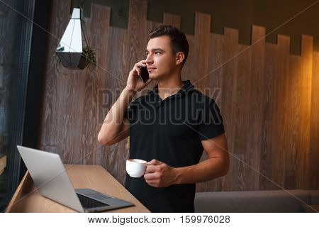 Mid adult business man standing and drinking a cup of coffee, looking out of window. Side view