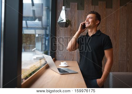 Fashionable and stylish young man talking on the phone, relaxing with coffee. Smiling handsome male with laptop at cafe