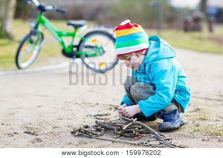 Cute little boy playing with wooden sticks in city park. Happy child in colorful clothes, spring or autumn. Creative games with kids outdoors in nature.