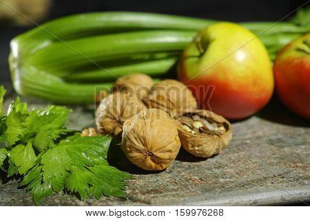 Ingredients for Waldorf salad - celery apples walnutes - fresh and healthy vegetables on granite board.