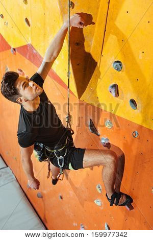 Balance and strength. Dexterous handsome young man spending time in climbing gym while climbing up the wall and using equipment.
